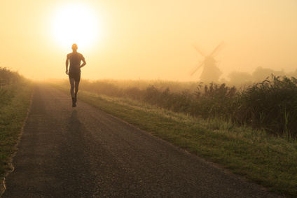 Man running in the foggy countryside near a windmill.