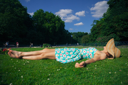 A young woman wearing a hat and a summer dress is relaxing on the grass